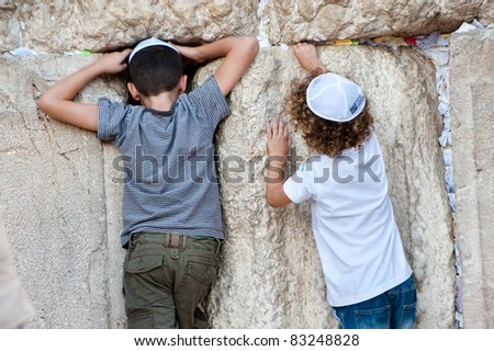 JERUSALEM - AUGUST 21: Jewish boys explore the Western Wall, the holiest site in Judaism, in the Old City of Jerusalem on Aug. 21, 2011. - stock photo