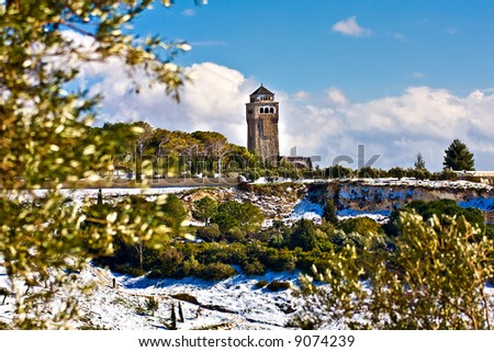 Jerusalem church tower with rare snow scenery between blurry olive trees (foreground olive trees out of focus) - stock photo