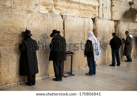 JERUSALEM - DECEMBER 30, 2013 - Orthodox jewish men pray at the Western Wall. An Important Jewish religious site located in the Old City of Jerusalem , Israel, 30.12.2013 - stock photo