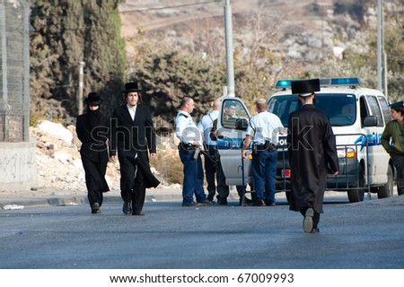 JERUSALEM - DECEMBER 3: Orthodox Jews pass Israeli police standing guard on Dec. 3, 2010, in the neighborhood of Sheikh Jarrah, historically an Arab Palestinian neighborhood in East Jerusalem.