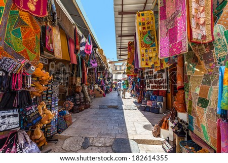 JERUSALEM, ISRAEL - AUGUST 21, 2013: Bazaar in Old City offer middle east traditional products, souvenirs and religious icons. It is very popular with tourists and pilgrims visiting Jerusalem, Israel. - stock photo