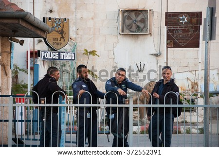 JERUSALEM, ISRAEL - FEBRUARY 19, 2014: Four police officers have coffee break at police station court. In an emergency, the police can be reached by dialing 100 from any telephone in Israel. - stock photo