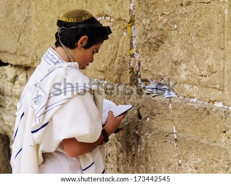 JERUSALEM, ISRAEL - FEBRUARY 25, 2010: Unidentified boy praying in front of the Wailing Wall. - stock photo