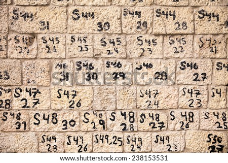 JERUSALEM, ISRAEL - JANUARY 26, 2013: Numbers and letters identify the order of stone blocks recently reconstructed as part of renovations of a historic wall near the Old City of Jerusalem in Israel. - stock photo