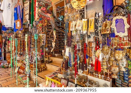 JERUSALEM, ISRAEL - JULY 10, 2014: Gift shop on bazaar in Old City of Jerusalem offers middle east traditional products, souvenirs and religious icons to tourists and pilgrims visiting the Holy Land. - stock photo