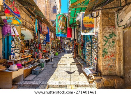 JERUSALEM, ISRAEL - JULY 10, 2014: Narrow stone street among stalls with traditional souvenirs and goods at bazaar in Old City - popular place among tourists and pilgrims visiting Jerusalem. - stock photo