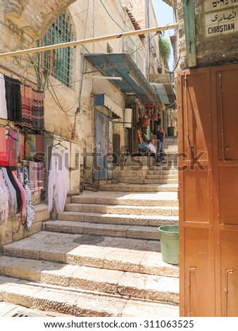 JERUSALEM, ISRAEL - JULY 13, 2015: Narrow stone street among stalls with traditional souvenirs and goods at bazaar in Old City - popular place among tourists and pilgrims visiting Jerusalem. - stock photo