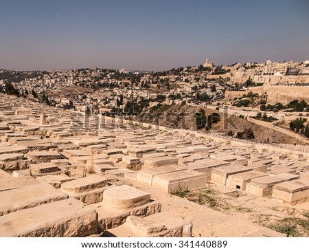 JERUSALEM, ISRAEL - July 13, 2015: Old jewish graves on the mount of olives in Jerusalem, with on the back the temple mount with the dome of the rock - stock photo