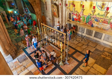 JERUSALEM. ISRAEL - JULY 16, 2015: People around Stone of Anointing and mosaic icon on the wall at the entrance to Holy Sepulcher church designate the place where Jesus' body was prepared for burial. - stock photo