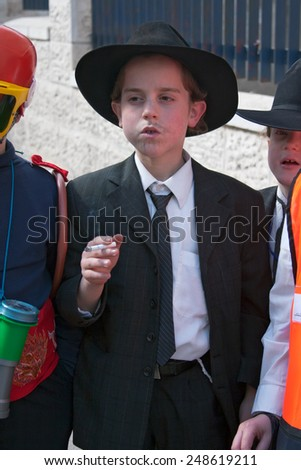 JERUSALEM, ISRAEL - MARCH 15, 2006: Purim carnival in the famous ultra-orthodox quarter of Jerusalem - Mea Shearim. Portrait of a boy children dressed in carnival costumes gangster.