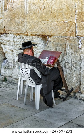 JERUSALEM, ISRAEL - MAY 26, 2013: Jew pray at the holy site. The Western Wall is the most sacred sites in Judaism, it attracts thousands of devotees every day in Jerusalem - stock photo