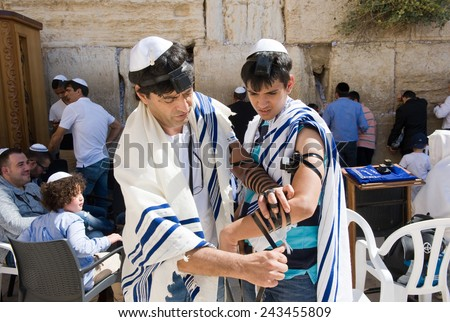 JERUSALEM, ISRAEL - OCT 06, 2014: A jewish man is preparing the tefillin around the arm of a boy of 13 years old before his Bar Mitzvah ritual at the Wailing wall in Jerusalem. - stock photo