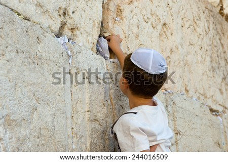 JERUSALEM, ISRAEL - OCT 06, 2014: A young jewish boy is putting a paper with a wish in a crack between the stones of the western wall in the old city of Jerusalem - stock photo