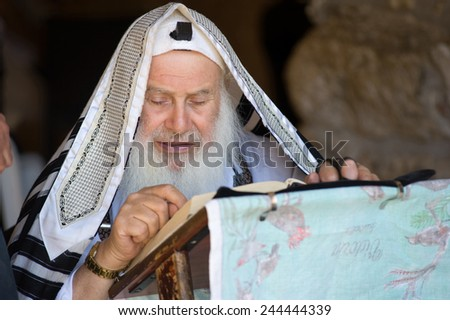 JERUSALEM, ISRAEL - OCT 06, 2014: An old jewish man is reading in the torah near the wailing wall in Jerusalem - stock photo