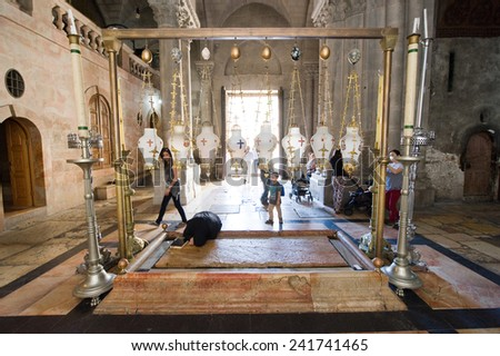 JERUSALEM, ISRAEL - OCT 06, 2014: The stone of the Anointing at the Church of the Holy Sepulchre. Also known as 'The Stone of Unction', on this place Jesus' body was prepared for burial. - stock photo