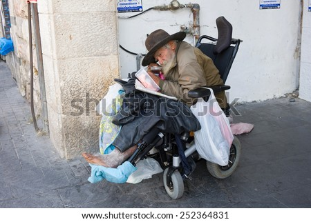 JERUSALEM, ISRAEL - 08 OCTOBER, 2014: A homeless man in a wheelchair in the streets of Jerusalem - stock photo