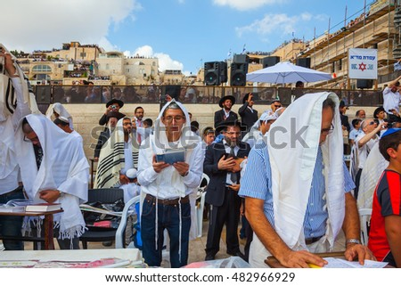 JERUSALEM, ISRAEL - OCTOBER 12, 2014:   Morning autumn Sukkot. The area in front of Western Wall of Temple filled with people. The Jews of ritual tallit are holding prayer