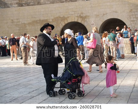 JERUSALEM, ISRAEL - OCTOBER 09, 2012: Traditional orthodox Judaic family on the square in front of the Wailing Wall - stock photo