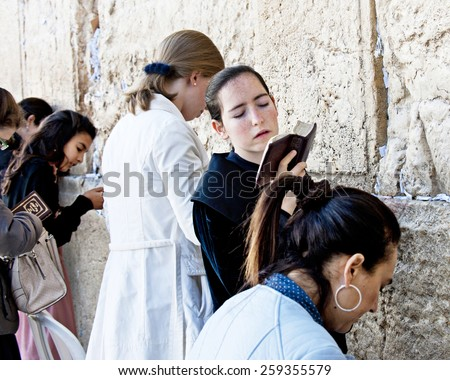 JERUSALEM, ISRAEL - OCTOBER 31, 2014:  Women praying at female side of Jerusalem's Western Wall.  Focus is on the center woman with prayer book.  She is twisting from side to side with closed eyes. - stock photo