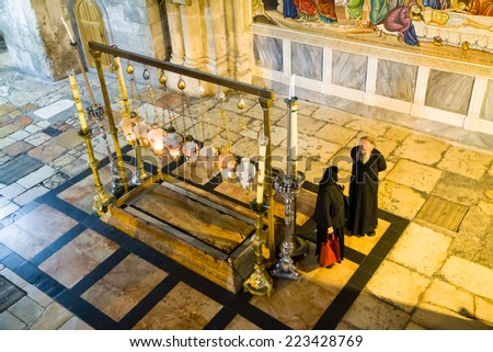 JERUSALEM. ISRAEL - SEPTEMBER 20, 2014: Stone of Anointing and mosaic icon on the wall at the entrance to Holy Sepulcher church designate the place where Jesus' body was prepared for burial. - stock photo
