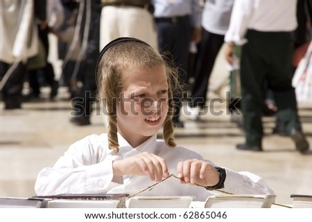 JERUSALEM, ISRAEL -SEPTEMBER 27: Unidentified boy prayer on September 27, 2010 at the Western Wall in Jerusalem,Israel. During jewish holiday of Sukkot. - stock photo