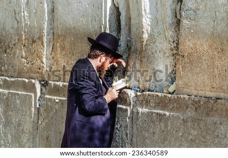 JERUSALEM - JAN 1,1994: Orthodox jewish man prays at the Western Wall in Jerusalem, Israel. Israel's annexation of East Jerusalem in 1967, including the Old City, was never internationally recognized. - stock photo