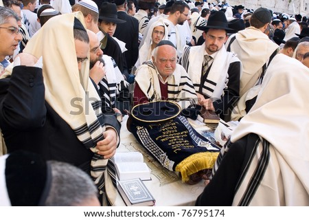 JERUSALEM JERUSALEM – APRIL 05: The Jewish Pesach (Passover) celebration at the Wailing Wall on April 05 2007. A group orthodox religious Jews wearing a prayer shawl draped around the Torah scroll. - stock photo