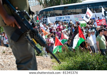 JERUSALEM - JULY 15: Israeli soldiers stand guard as thousands of Israeli, Palestinian, and international activists march in support of Palestinian rights through East Jerusalem on July 15, 2011. - stock photo