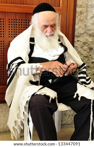 JERUSALEM  - JULY 28:Jewish Man wrapped in talit pray at the Western Wall on July 28 2009 in Jerusalem, Israel.It's the most sacred site by the Jewish faith outside of the Temple Mount itself. - stock photo