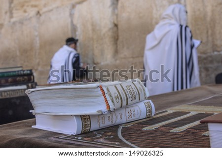 JERUSALEM - JULY 31 - Orthodox Jews prays at the Western Wall, behind praying book (Siddur) - July 31, 2013 in the old city of Jerusalem, Israel. This is the holiest place in Jewish tradition