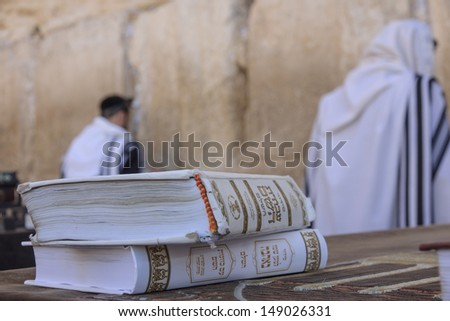 JERUSALEM - JULY 31 - Orthodox Jews prays at the Western Wall, behind praying book (Siddur) - July 31, 2013 in the old city of Jerusalem, Israel. This is the holiest place in Jewish tradition - stock photo