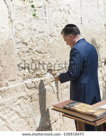 JERUSALEM - JULY 29 :  US Republican presidential candidate Mitt Romney places a mesage written on paper in the stones of the Western wall during his visit to Jerusalem, Israel on July 29, 2012 - stock photo