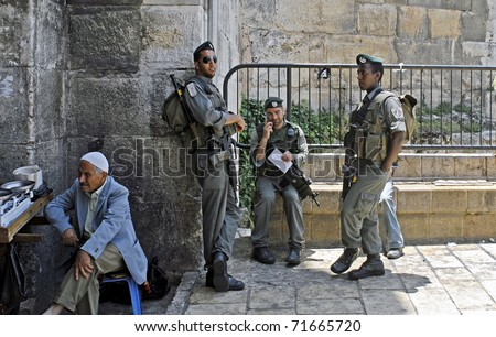JERUSALEM - JUNE 11: Israeli Border Guard stand at Damascus Gate of Old City with Jewish merchant and scales sitting left at gate entrance into the Old City on June 11, 2007 in Jerusalem.