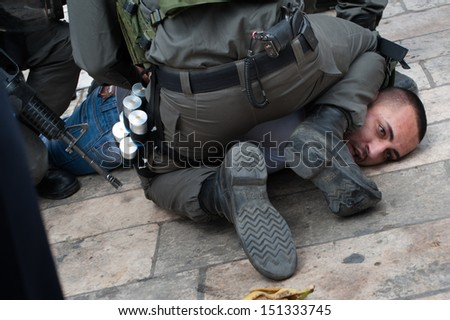 JERUSALEM - MAY 15: Israeli police arrest a Palestinian man during clashes with Palestinians commemorating Nakba Day at Damascus Gate, East Jerusalem, May 15, 2013. - stock photo