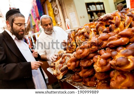 JERUSALEM - MAY 13: Orthodox Jewish man buys challah at pre-shabbat market on May 13, 2011. - stock photo