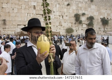 JERUSALEM-OCT 02: The Jews  at the Western Wall during Jewish holiday of Sukkot, October 2, 2012 in Jerusalem, Israel.Etrog and Lulav is two of four species used during of Sukkot.  - stock photo