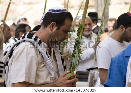 JERUSALEM-OCT 02: The Jews in prayer at the Western Wall during Jewish holiday of Sukkot, October 2, 2012 in Jerusalem, Israel.Etrog and Lulav is two of four species used during of Sukkot.  - stock photo