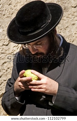 JERUSALEM - OCTOBER 20: Jewish ultra-orthodox man inspect Etrog at a four species market in Mea Shearim for the Jewish holiday of Sukkot on October 20 2005 in  in Jerusalem, Israel.