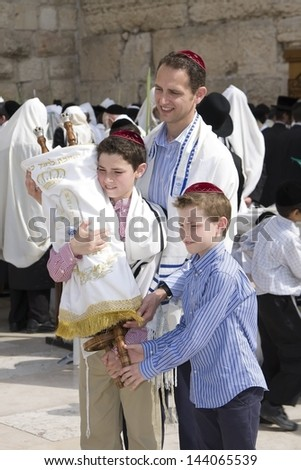 JERUSALEM -OCTOBER 02: Unidentified boys with his father at the Western Wall during Jewish holiday of Sukkot October 02, 2012 in Jerusalem, Israel. - stock photo