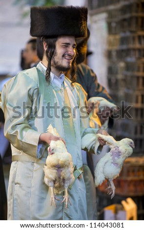 JERUSALEM - SEP 25 : An ultra Orthodox Jewish man holds chickens during the Kaparot ceremony held in Jerusalem Israel in September 25, 2012 - stock photo