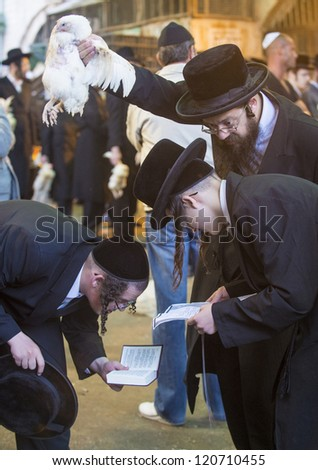 JERUSALEM - SEP 25 : An ultra Orthodox Jewish men prays with a chicken during the Kaparot ceremony held in Jerusalem Israel in September 25 2012 - stock photo