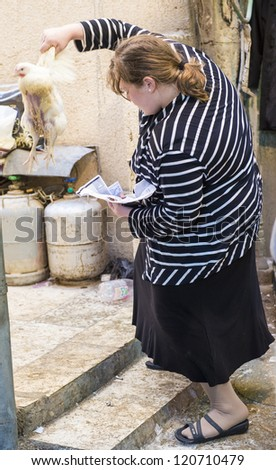JERUSALEM - SEP 25 : An ultra Orthodox Jewish woman waves a chicken over her head during the Kaparot ceremony held in Jerusalem Israel in September 25 2012 - stock photo