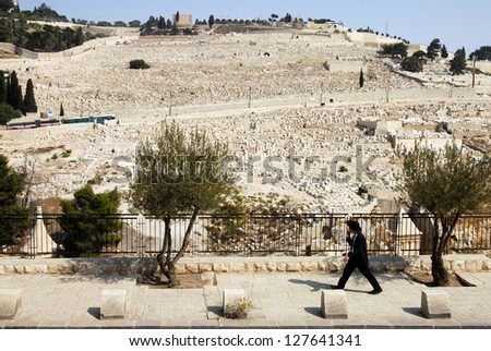 JERUSALEM - SEP 28:Jewish orthodox man pass by Mount of Olives on September 28 2007 in Jerusalem ,Israel. The Jewish cemetery on Mt olives is over 3,000 years and holds approximately 150,000 graves. - stock photo