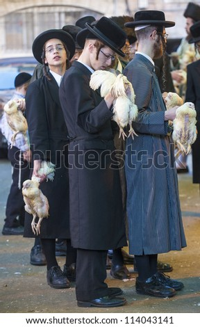 JERUSALEM - SEP 25 : ultra Orthodox Jewish men holds chickens during the Kaparot ceremony held in Jerusalem Israel in September 25, 2012 - stock photo