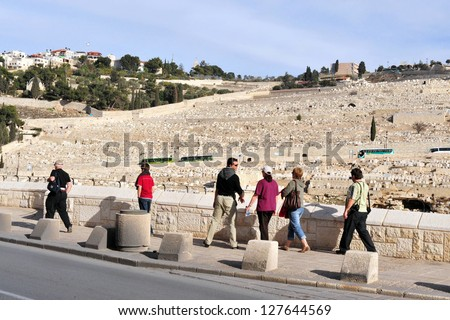 JERUSALEM - SEP 28:Visitors pass by Mount of Olives on September 28 2007 in Jerusalem ,Israel. The Jewish cemetery on Mt olives is over 3,000 years and holds approximately 150,000 graves. - stock photo