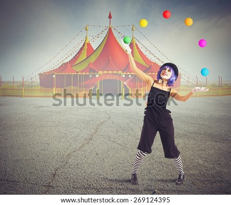 Jester clown in front of circus tent - stock photo