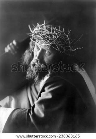 Jesus Christ, man personifying Jesus Christ, wearing crown of thorns and carrying cross, ca 1910. - stock photo