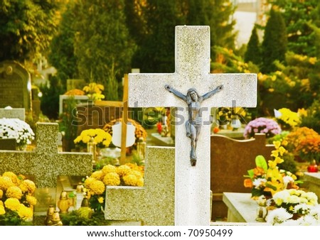 jesus christ on cemetery cross and flowers on the All Saints Day, Wroclaw, Poland - stock photo