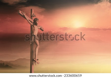 Jesus christ on the cross over a sunset background. - stock photo