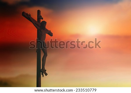 Jesus christ on the cross over blurred sunset background. - stock photo